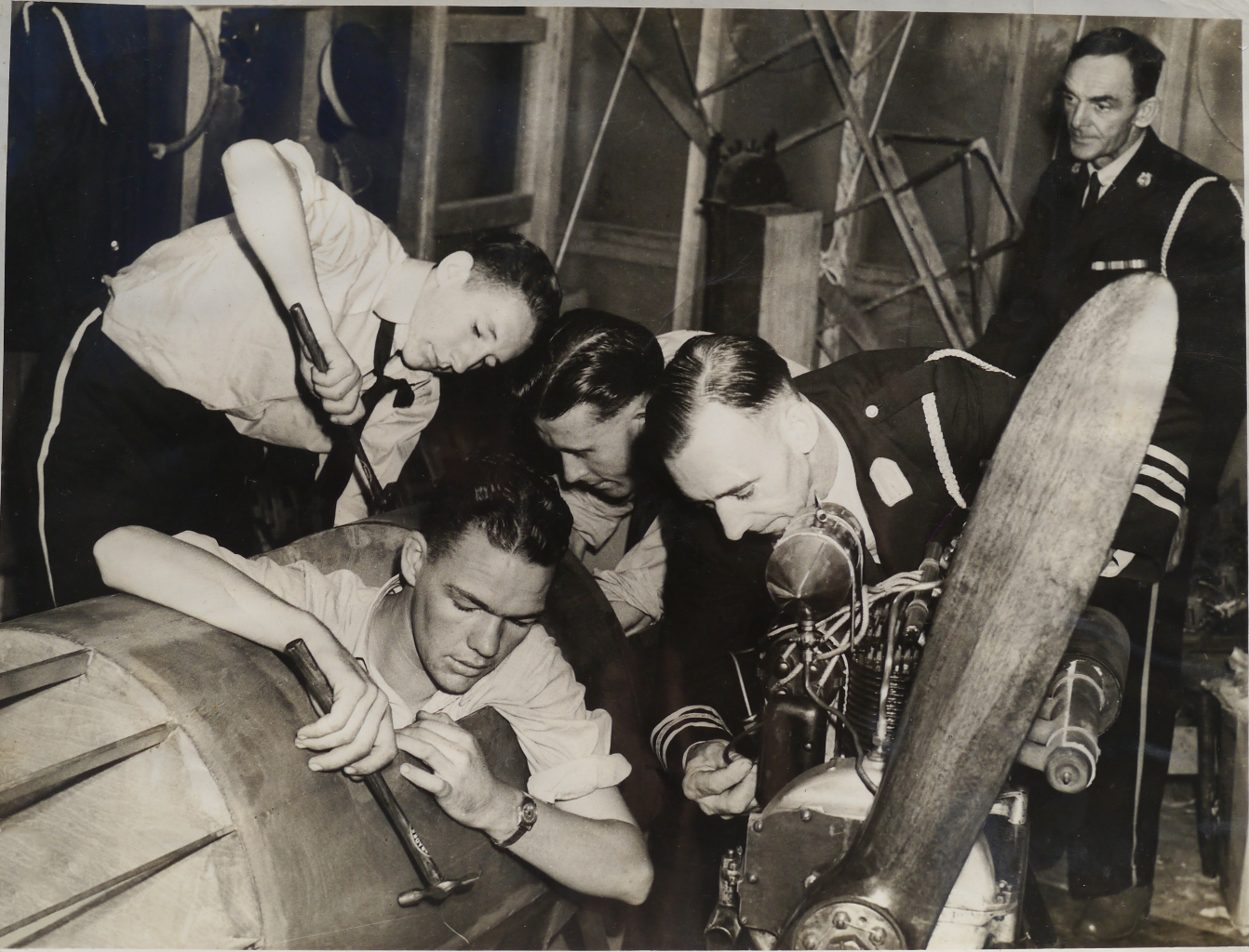 "The newspaper caption reads  ""...practical lessons in aeroplane construction. Cadets C. Perrett, L. Brown and C.Noonan are seen with Divisional Commander J. Cox working on the fuselage and engine of their own ground plane."""
